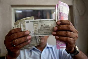 A cashier checks Indian rupee notes inside a room at a fuel station.(Representative image)