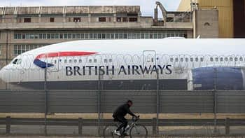 A cyclist passes a passenger aircraft, operated by British Airways, a unit of International Consolidated Airlines Group SA (IAG) grounded at London Heathrow Airport in London, U.K., on Monday, June 8, 2020.