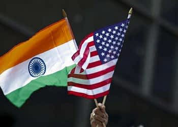 A man holds the flags of India and the US while people take part in the 35th India Day Parade in New York.