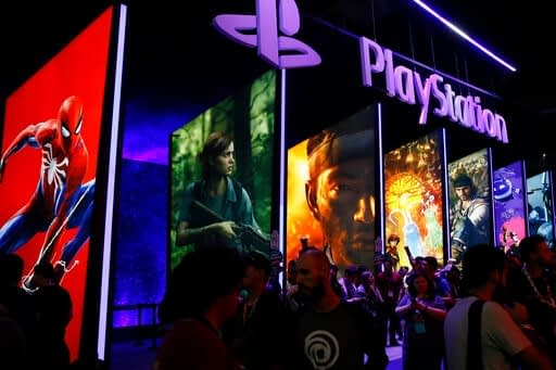 FILE - In this June 14, 2018, file people stand online next to the PlayStation booth at the 24th Electronic Entertainment Expo E3 at the Los Angeles Convention Center. Sony said Wednesday, Sept. 16, 2020 its upcoming PlayStation 5 video game console will cost $500 and launch Nov. 12, setting up a holiday battle with Microsoft